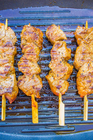 pan fried round steak cubes on sticks on a grill pan Stock Photo