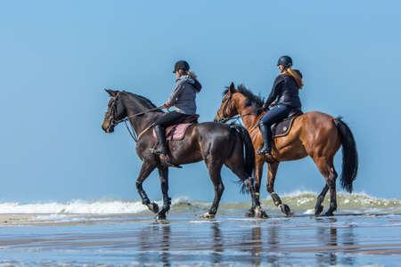 dutch girl: Kijkduin, the Netherlands - March 24, 2017: horseback riders enjoying the spring weather on the beach