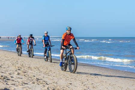 Kijkduin, the Netherlands - April 2, 2017: group of men riding bikes on sunny beach