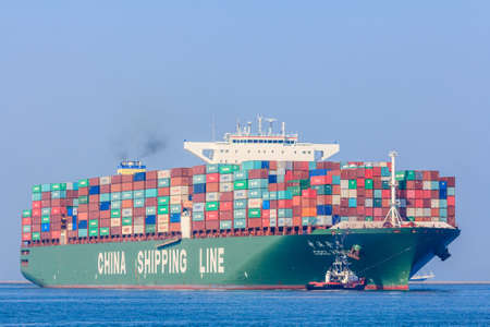 starboard: Rotterdam, the Netherlands - April 9, 2017: CSCL Venus container ship with tug boats in Rotterdam harbor