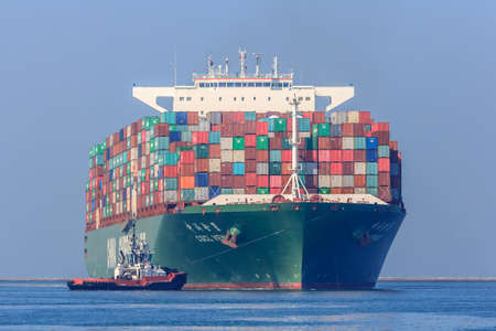 tonne: Rotterdam, the Netherlands - April 9, 2017: CSCL Venus container ship with tug boats in Rotterdam harbor