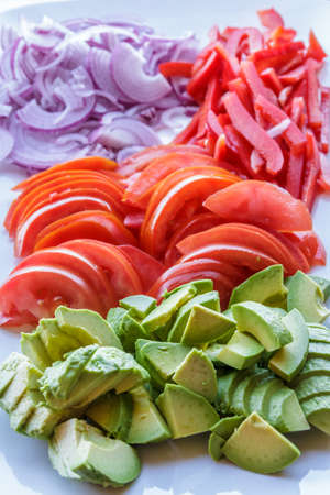 delicious piles of freshly sliced avacado, tomato and onion on serving plate