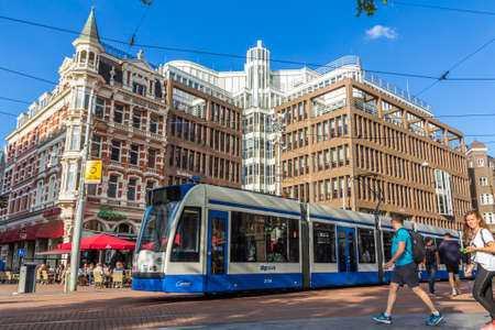 Rembrandtplein Amsterdam, the Netherlands - 13 August 2017: tram passing tourists on Rembrandtplein Amsterdam
