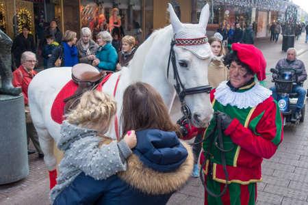 Den Haag, Nederland - 26 november 2016: schoorsteenpete in menigte met het paard van Sinterklaas