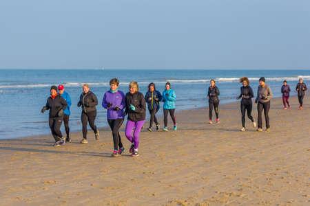 Kijkduin, The Hague, the Netherlands - 14 January 2017: senior running club jogging on sandy beach