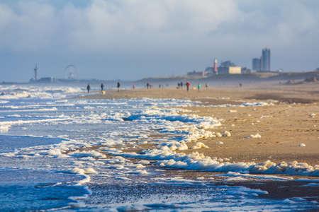 north sea storm blowing foam from sea onto Kijkduin beach, the Netherlands