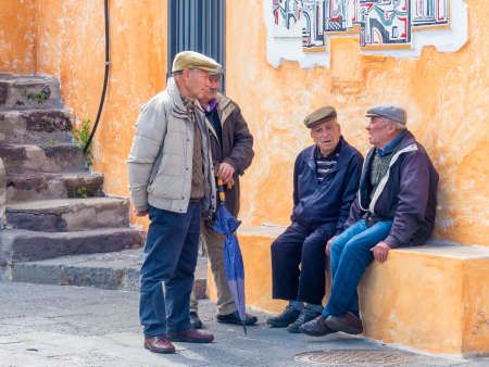 Sardinia, Italy - May 5 2018: group of male elderly Sardinian villages talking on the street