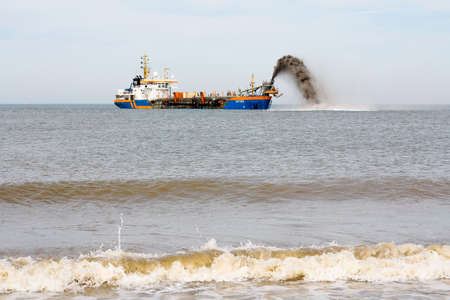 Kijkduin, The Hague, the Netherlands - April 2 2011: Ship pumping sand onto beach for coastal defense Éditoriale