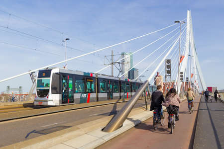 Rotterdam, the Netherlands - April 7 2018; people riding bikes over Rotterdam Erasmus bridge crossing Maas river with RET tram in background Redakční