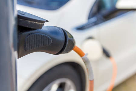hybrid electric car charging at plug in station