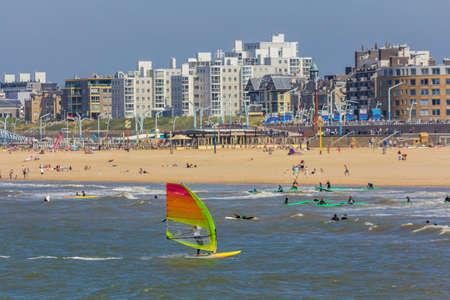 Scheveningen, The Hague, the Netherlands - June 27 2018: speeding windsurfers sailing off the beach of popular Dutch beach resort Scheveningen with the pier and ferris wheel in the background 報道画像
