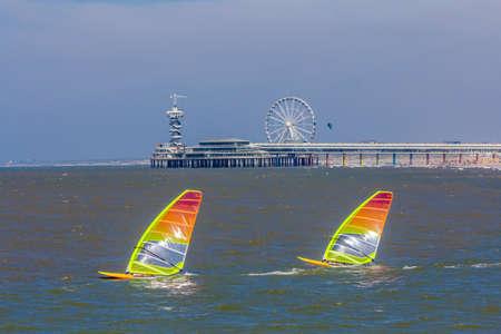 Scheveningen, The Hague, the Netherlands - June 27 2018: speeding windsurfers sailing off the beach of popular Dutch beach resort Scheveningen with the pier and ferris wheel in the background Editorial