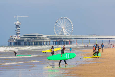 cheveningen, the Netherlands - June 27 2018: group of young people with surf boards on Scheveningen beach near pier