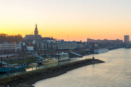 Nijmegen, the Netherlands - November 16 2018: Nijmegen waterfront view with ferries and boats from above during sunset