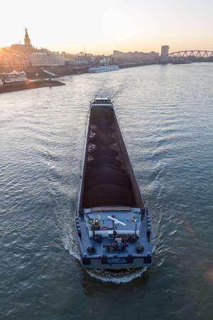 Nijmegen, the Netherlands - November 16 2018: cargo river barges passing near Nijmegen during sunset