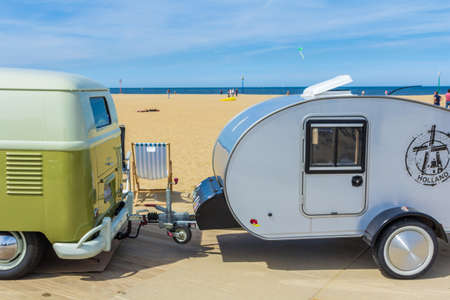 Scheveningen beach, the Netherlands - May 21, 2017: Green VW kombi camper wagen and teardrop trailer at Aircooled classic car show