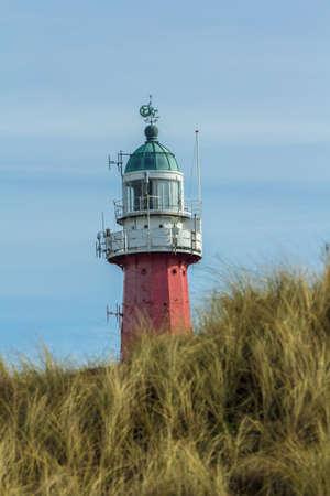 Scheveningen, the Netherlands - March 12 207: historic dutch lighthouse on the dunes of Scheveningen beach serving as a navigation aid to fishermen and sea travellers Editorial