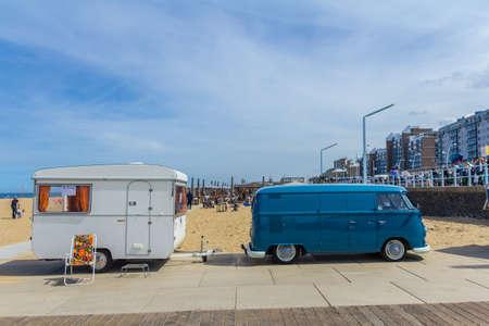 Scheveningen beach, the Netherlands - May 21, 2017: Blue VW kombi camper wagen and caravan trailer at Aircooled classic car show