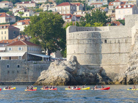 Dubrovnik Croatia - August 6 2018: canoe water sport tour on the Adriatic sea outside Dubrovnik old town walled city and new town with modern town architecture Imagens - 115968647