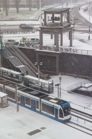 Amsterdam, the Netherlands - January 22 2019: GVB fast tram riding through Amsterdam in snow view from above Imagens - 115968669