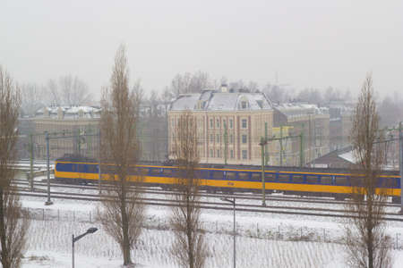 Amsterdam, the Netherlands - January 22 2019: Dutch electric intercity train riding through Amsterdam in snow view from above