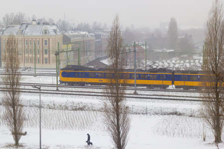 Amsterdam, the Netherlands - January 22 2019: Dutch electric intercity train riding through Amsterdam in snow view from above Imagens - 115968672