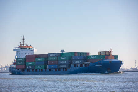 Hoek van Holland, the Netherlands - January 20 2019: cargo shipping container vessel mirror sailing out of port Rotterdam past Hoek van Holland and Maasvlakte harbour Imagens - 115968692