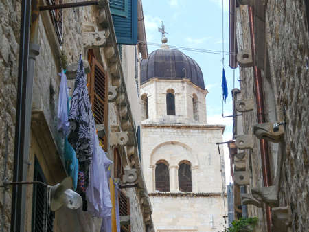 Dubrovnik, Croatia - August 3 2018: Dubrovnik church tower viewed from washing lined street Imagens - 115968891