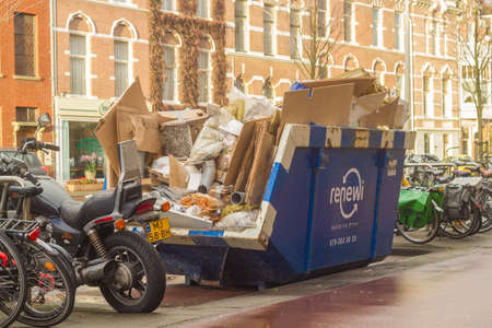 The Hague, the Netherlands - June 28, 2019: rubbish skip full of cardboard, pipe and housing material on busy city street Editorial