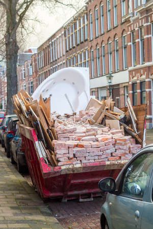 The Hague, the Netherlands - June 28, 2019: rubbish skip full of bricks, jacuzzi hot tub and wood on busy city street Editorial