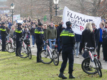 Malieveld, The Hague, the Netherlands - February 7 2019: school children skipping school to protest against climate change policy, watched by cordon of bike police
