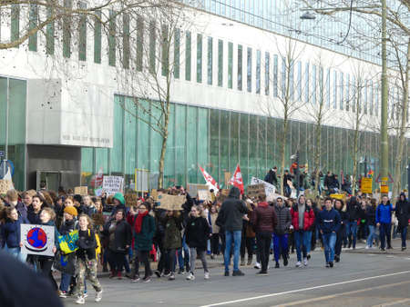 The Hague, the Netherlands - February 7 2019: students at anti climate change protest in The Hague with banners walking through the city
