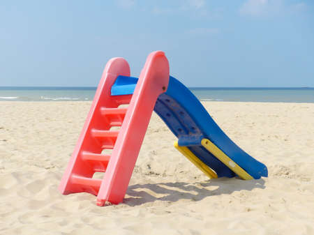 playground slide on beautiful deserted beach with blue sky and water 스톡 콘텐츠