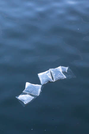 plastic marine pollution, underwater plastic bags and packaging floating semi submerged at surface of water