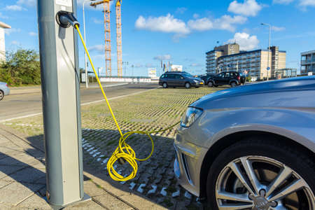 Kijkduin, the Netherlands - September 15 2018: electric hybrid car charging batteries at plug in charge station in the Netherlands