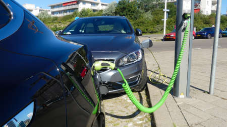 Kijkduin, the Netherlands - June 29 2019: Tesla electric car and hybrid volvo charging batteries at plug in charge station in the Netherlands
