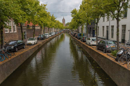 Delft, the Netherlands - July 19 2019 : view of historic oude canal leading to  view of the  Oude Kerk in Delft