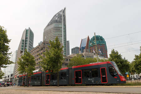 The Hague, the Netherlands - July 19 2019: tall buildings of The Hague city skyline with fast tram in foreground