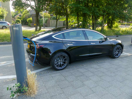 Kijkduin, the Netherlands - July 19 2019: Tesla model electric car charging batteries at plug in charge station in leafy green suburb inthe Netherlands