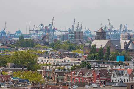 Rotterdam, the Netherlands - July 19 2019: mixed classic architecture of Rotterdam leafy urban apartment buildings in foreground with harbour waterfront port cranes in background Editorial