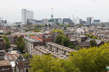 Rotterdam, the Netherlands - July 19 2019: mixed classic architecture of Rotterdam leafy urban apartment buildings in foreground with modern city high rise, tall towers and euro mast in background
