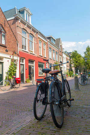 Haarlem, The Netherlands - July 19, 2019: pleasant quiet street in the city center of Haarlem with a historic dutch architecture and small houses and bicycles in the foreground