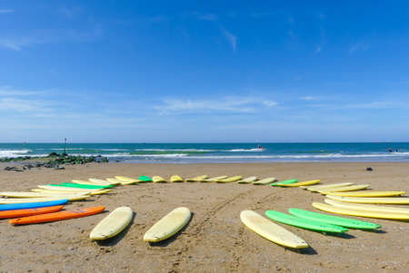 colourful surfboards in a circle on sunny beach with blue sky and sea