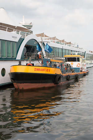 Amsterdam, the Netherlands - August 21 2019: Rhine river cruise ship being refueled by a fuel boat in the Dutch harbour of amsterdam