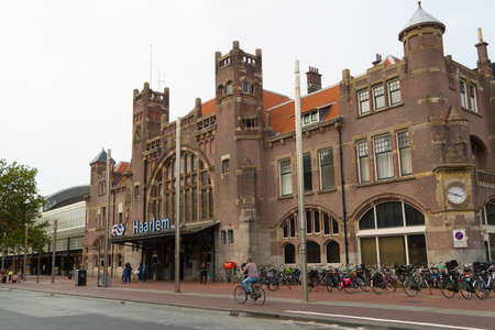 Haarlem, The Netherlands - July 19, 2019: historic style dutch architecture of Haarlem central train station with cyclist in foreground Editorial