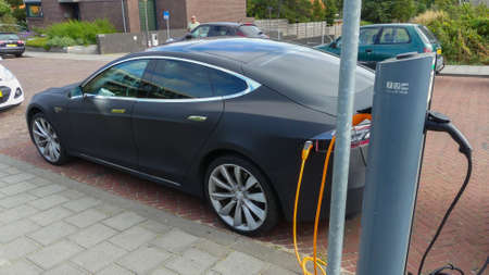 Kijkduin, the Netherlands - September 15 2019: Tesla electric car charging batteries at plug in charge station in the Netherlands