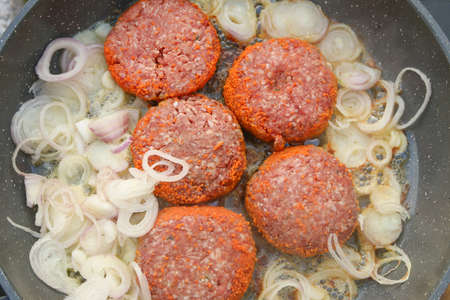 raw uncooked burgers with caramelising onions cooking in a deep fry pan top view Imagens