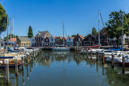 middleharnis, Goeree overflakkee, the Netherlands - July 14 2018: stunning views over historic dutch yacht harbour with classic dutch historical houses and bike riders