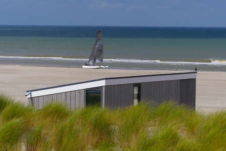 Kijkduin, the Netherlands - August 14 2019: scenic beach scene with green dune grass, holiday cabin and sailing yacht 新聞圖片