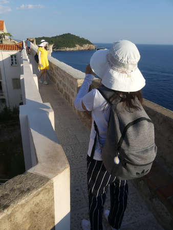 old town Dubrovnik, Croatia - August 4 2018: tourists walking along the wall of Dubrovnik old town with brightly coloured sun hats 新聞圖片